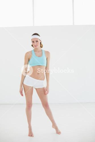 Beautiful slender woman posing in sportswear in sports hall