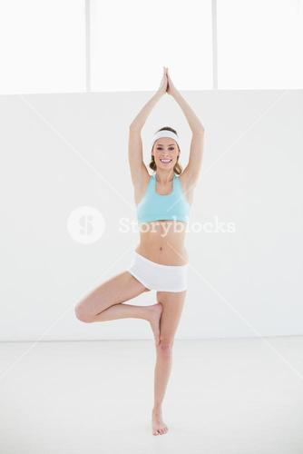 Happy slim woman doing yoga pose in sports hall