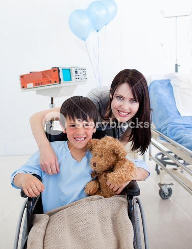 Smiling little boy sitting on wheelchair and his mother