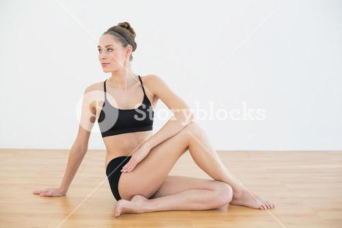 Cute toned woman stretching her body sitting on floor