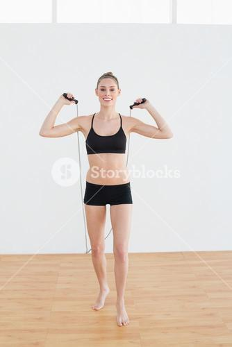 Gleeful slender woman holding a rope for skipping