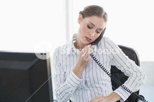 Serious chic businesswoman phoning with telephone