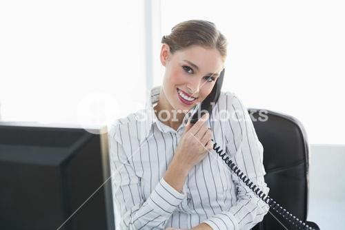 Gleeful chic businesswoman phoning with telephone sitting at her desk