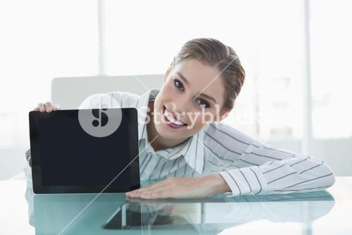 Attractive chic businesswoman showing tablet sitting at desk