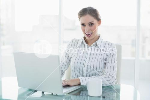 Gleeful lovely chic businesswoman sitting at her desk using her notebook