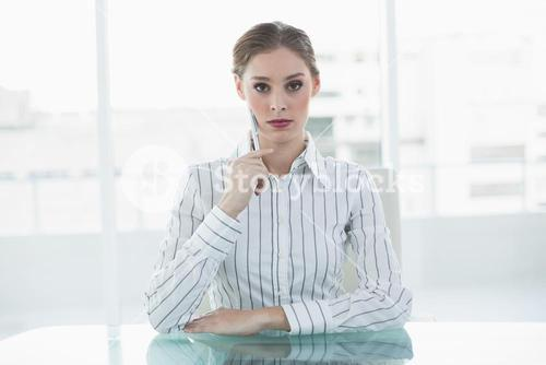 Concentrating chic businesswoman sitting thinking at her desk