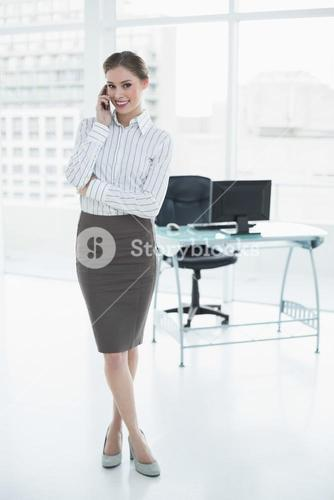 Gleeful calm businesswoman phoning with her smartphone standing in her office