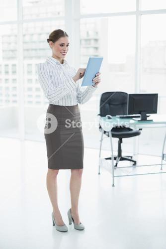 Happy chic businesswoman using her tablet