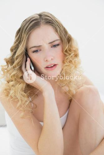 Pretty upset blonde sitting on bed phoning