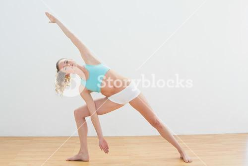 Calm slim blonde standing in extended side angle pose