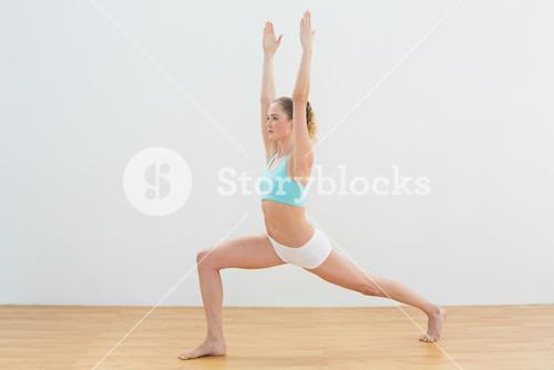 Concentrating slim blonde standing in high lunge pose