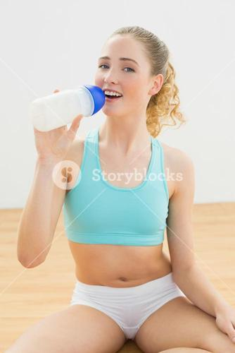 Smiling slim blonde sitting on floor drinking from sports bottle