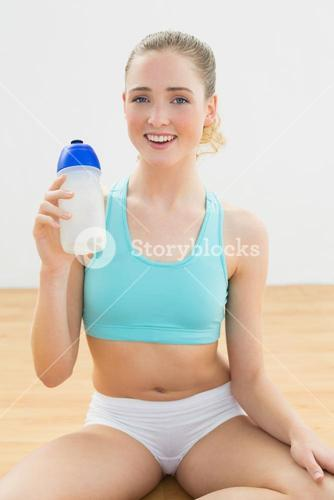 Cheerful slim blonde sitting on floor drinking from sports bottle