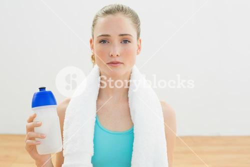 Unsmiling slim blonde sitting on floor holding sports bottle