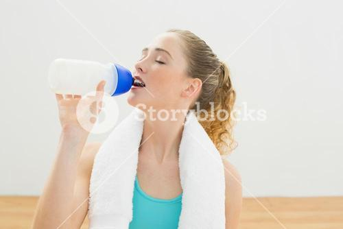 Content slim blonde sitting on floor drinking from sports bottle