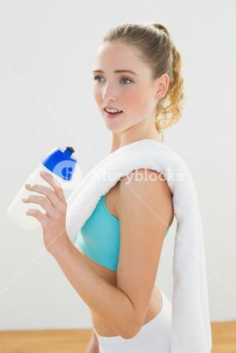 Calm slim blonde standing and holding sports bottle