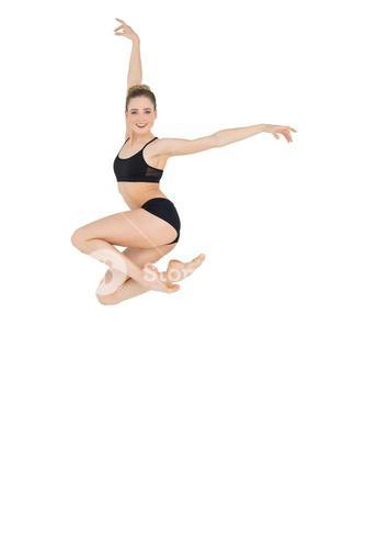 Cheerful slim ballet dancer jumping in the air