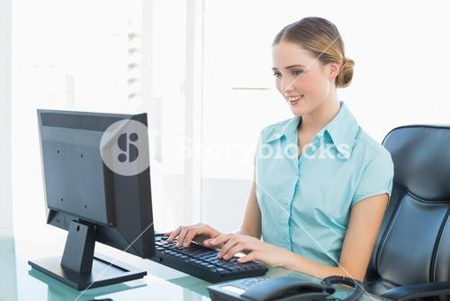 Classy happy businesswoman working at computer