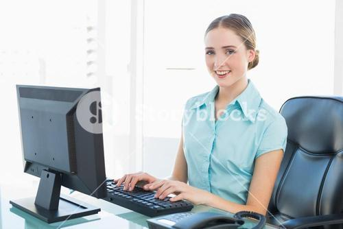 Classy smiling businesswoman working at computer
