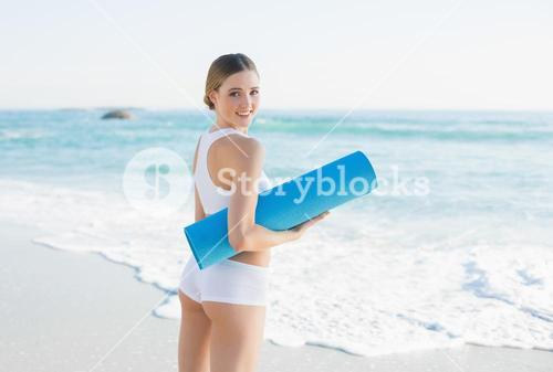 Smiling slender woman holding rolled up exercise mat