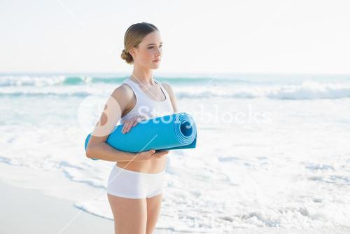 Content slender woman holding rolled up exercise mat