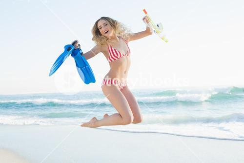 Happy woman jumping while holding flippers and a snorkel and diving goggles