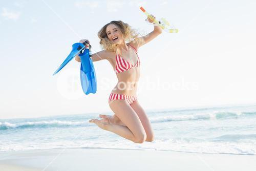 Cheerful woman jumping on beach