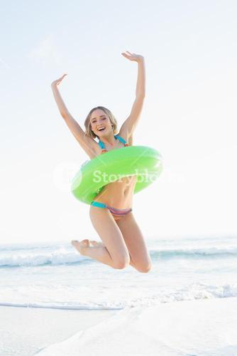Cheerful young woman holding a rubber ring while jumping on a beach