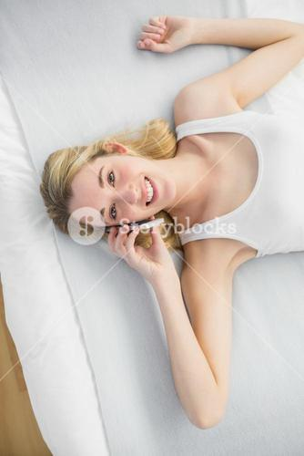 Content peaceful woman phoning with her smartphone while lying on her bed