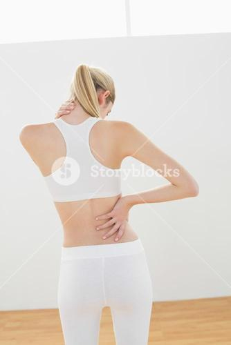 Sporty blonde woman touching her injured nape