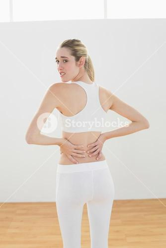 Suffering sporty woman touching her injured back