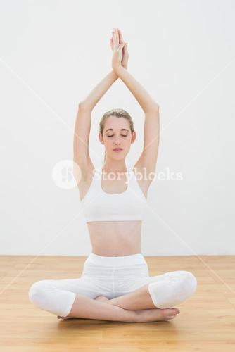 Attractive calm woman practising yoga sitting in lotus position in sports hall