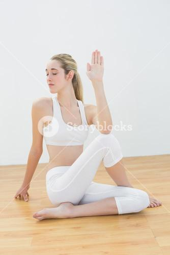 Concentrated young woman stretching her body sitting in sports hall