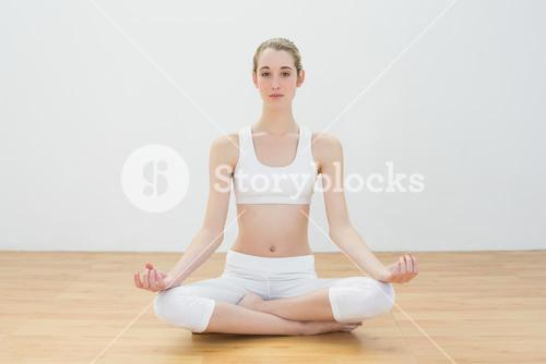 Focused calm woman meditating sitting in sports hall