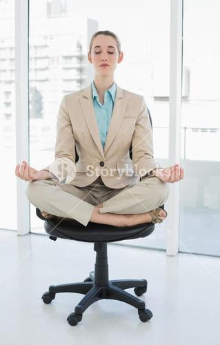Peaceful chic businesswoman sitting in lotus position on swivel chair