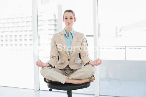 Lovely chic businesswoman sitting in lotus position on her swivel chair