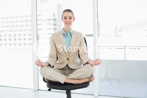 Content classy businesswoman sitting in lotus position on her swivel chair