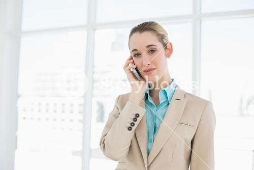 Pretty chic businesswoman phoning with her smartphone