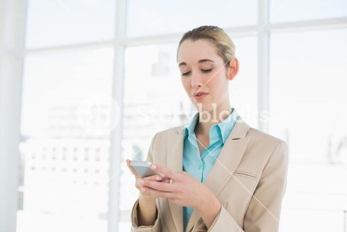 Concentrated chic businesswoman texting with her smartphone
