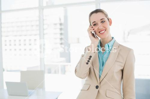 Cute smiling chic businesswoman phoning with her smartphone