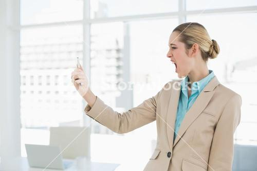 Attractive young businesswoman looking shocked at her smartphone