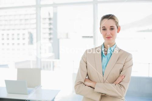Chic businesswoman posing confidently with arms crossed