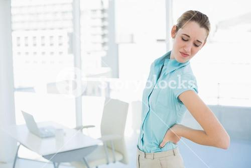 Gorgeous suffering businesswoman holding her injured back