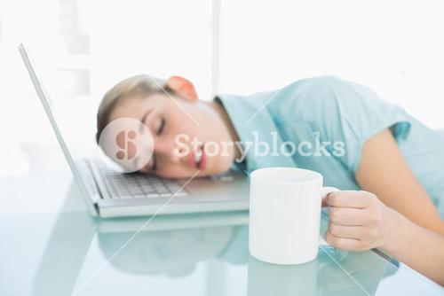 Calm businesswoman napping sitting on her swivel chair