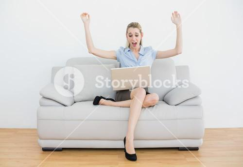 Extremely cheering chic businesswoman sitting on her couch