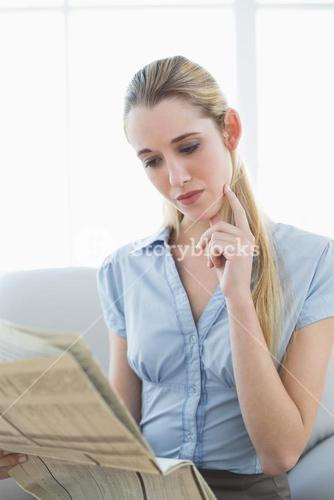 Concentrated chic businesswoman reading newspaper sitting on couch