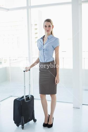 Classy businesswoman posing standing in office holding a suitcase