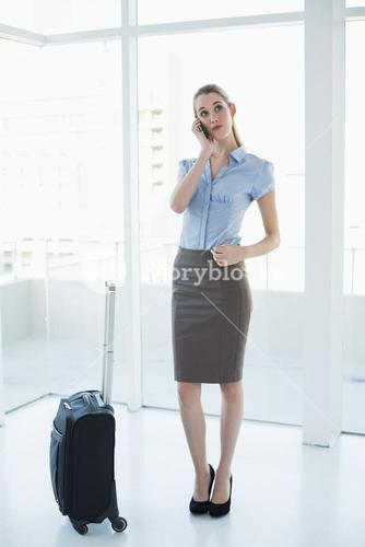 Thoughtful chic businesswoman phoning while standing in the office