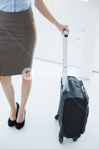 Mid section on slender classy businesswoman holding a suitcase