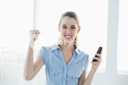 Cheering chic businesswoman holding her smartphone
